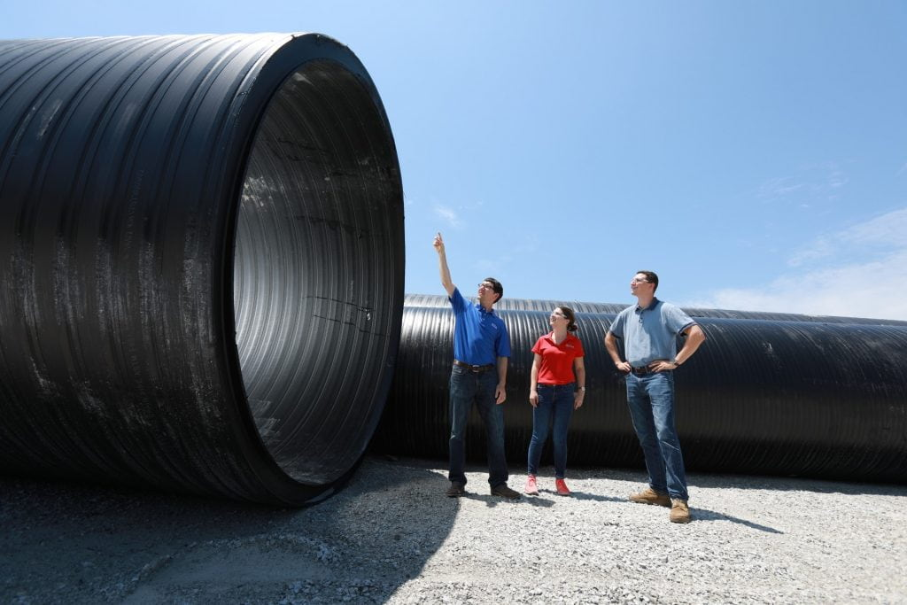 ISCO employees next to a large diameter HDPE pipe