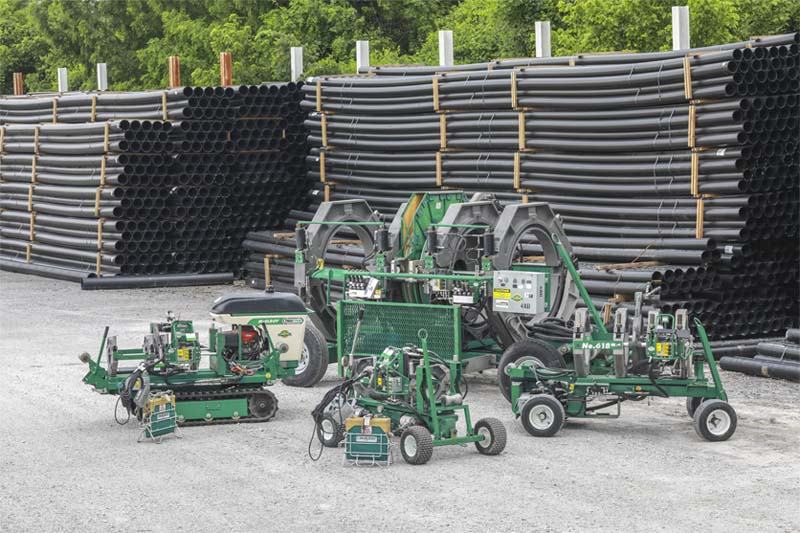 McElroy fusion machines in front of stacked HDPE pipes