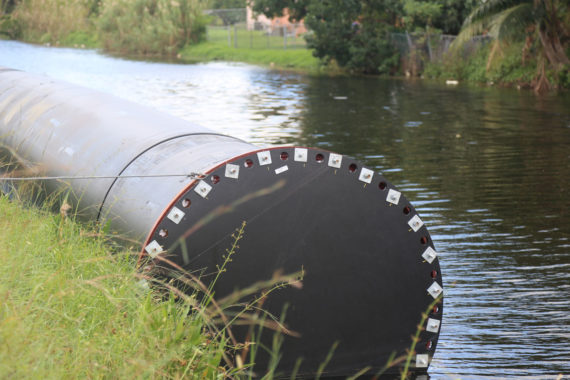 A large diameter 63-inch pipe tied to the side of a stream