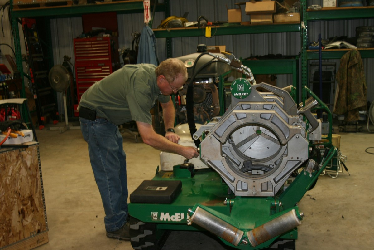 An ISCO team member performing maintenance on a McElroy fusion machine
