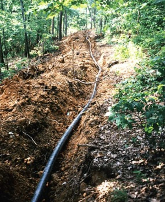 HDPE pipe in an excavated ditch running through woods in Dalton, Georgia